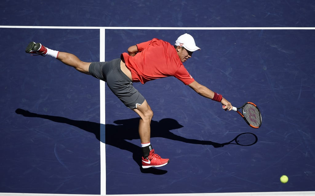 Kei Nishikori of Japan stretches for a backhand against Dan Evans of Great Britain at Indian Wells Tennis Garden on March 12, 2017 in Indian Wells, California.