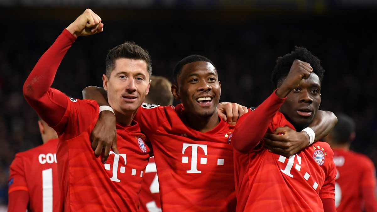 Robert Lewandowski of Bayern Munich celebrates with David Alaba and Alphonso Davies after he scores his team's third goal during the UEFA Champions League round of 16 first leg match between Chelsea FC and FC Bayern Muenchen