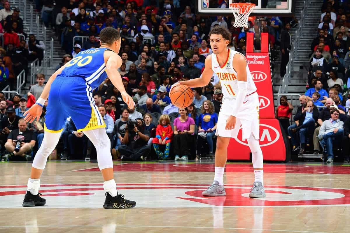 Trae Young and Stephen Curry in action during Atlanta Hawks vs Golden State Warriors game in 2018
