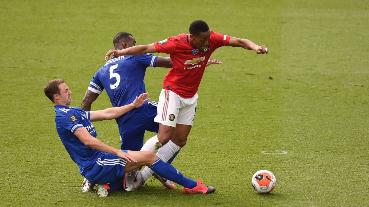 Anthony Martial is sent tumbling under pressure from Wes Morgan and Jonny Evans to win a penalty for Manchester United