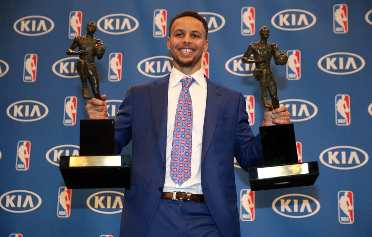 Steph Curry holds his two MVP awards