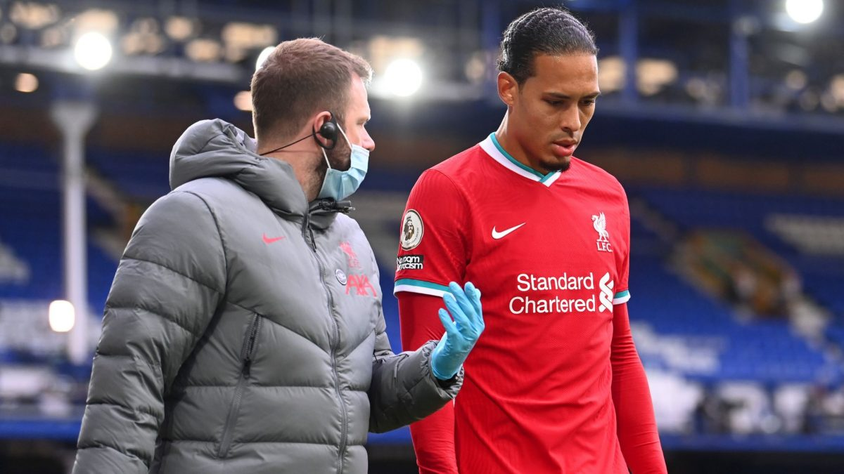 Virgil van Dijk being consulted with a doctor after his injury during Liverpool's 2-2 draw with Everton