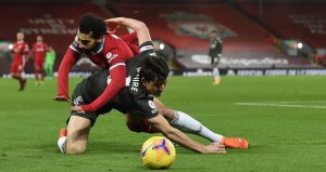 A tussle between Harry Maguire and Mohamed Salah sees both players go to ground