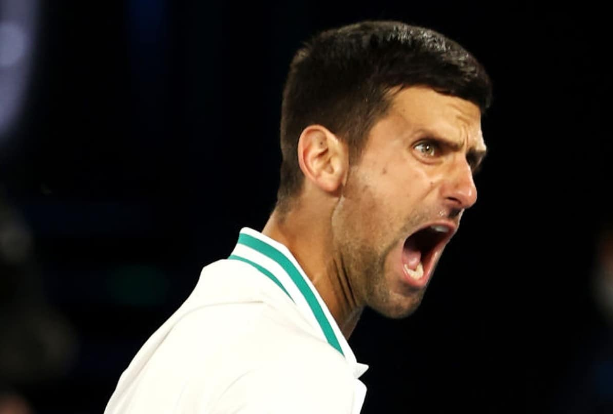 Novak Djokovic of Serbia reacts in his Men's Singles fourth round match against Milos Raonic of Canada during day seven of the 2021 Australian Open at Melbourne Park on February 14, 2021 in Melbourne, Australia. (Photo by Cameron Spencer/Getty Images)