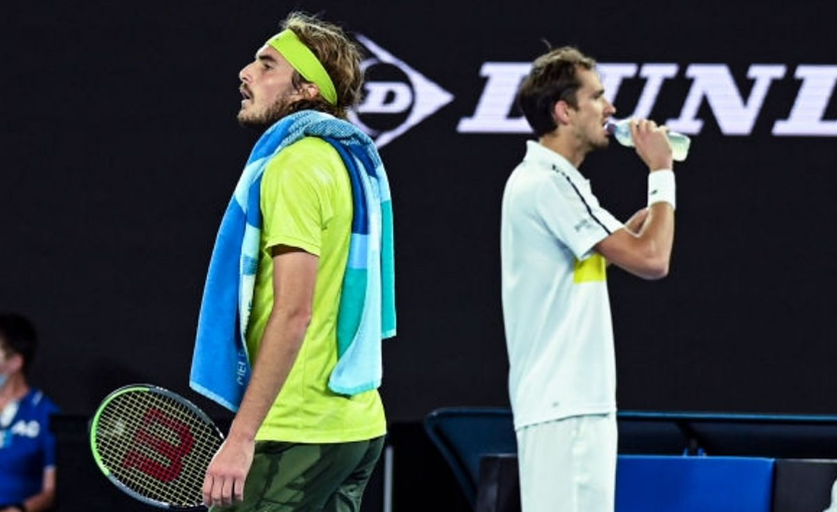 Stefanos Tsitsipas of Greece passes Daniil Medvedev of Russia at a change of ends in the men's singles semi-finals during day 12 of the 2021 Australian Open at Melbourne Park on February 19, 2021 in Melbourne, Australia. (Photo by TPN/Getty Images)