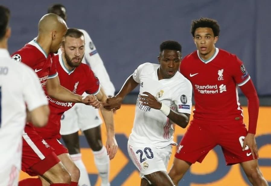 Vinicius Junior (2nd R) of Real Madrid in action against Arnold Alexander (R) of Liverpool during the UEFA Champions League quarter final match between Real Madrid and Liverpool at Alfredo Di Stefano Stadium in Madrid, Spain on April 06, 2021. (Photo by Senhan Bolelli/Anadolu Agency via Getty Images)