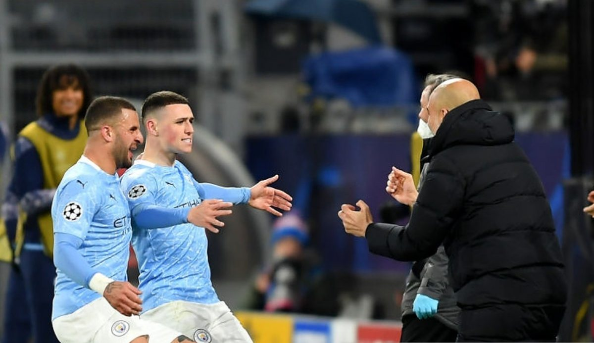 Phil Foden of Manchester City runs towards Pep Guardiola, Manager of Manchester City as he celebrates with team mate Kyle Walker (L) after scoring their side's second goal during the UEFA Champions League Quarter Final Second Leg match between Borussia Dortmund and Manchester City at Signal Iduna Park on April 14, 2021 in Dortmund, Germany. Sporting stadiums around Germany remain under strict restrictions due to the Coronavirus Pandemic as Government social distancing laws prohibit fans inside venues resulting in games being played behind closed doors. (Photo by Frederic Scheidemann/Getty Images)